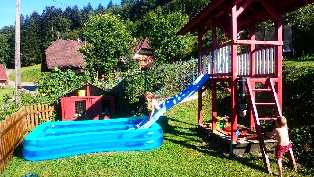 Im Sommer Spielturm mit Wasserrutsche und Schwimmbecken